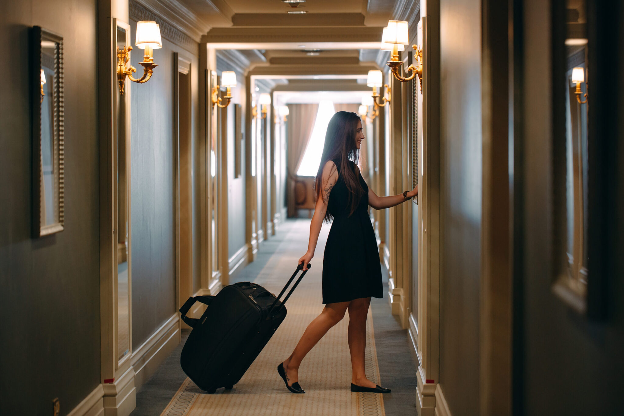 Guest with suitcase enters hotel room with hotel phone system