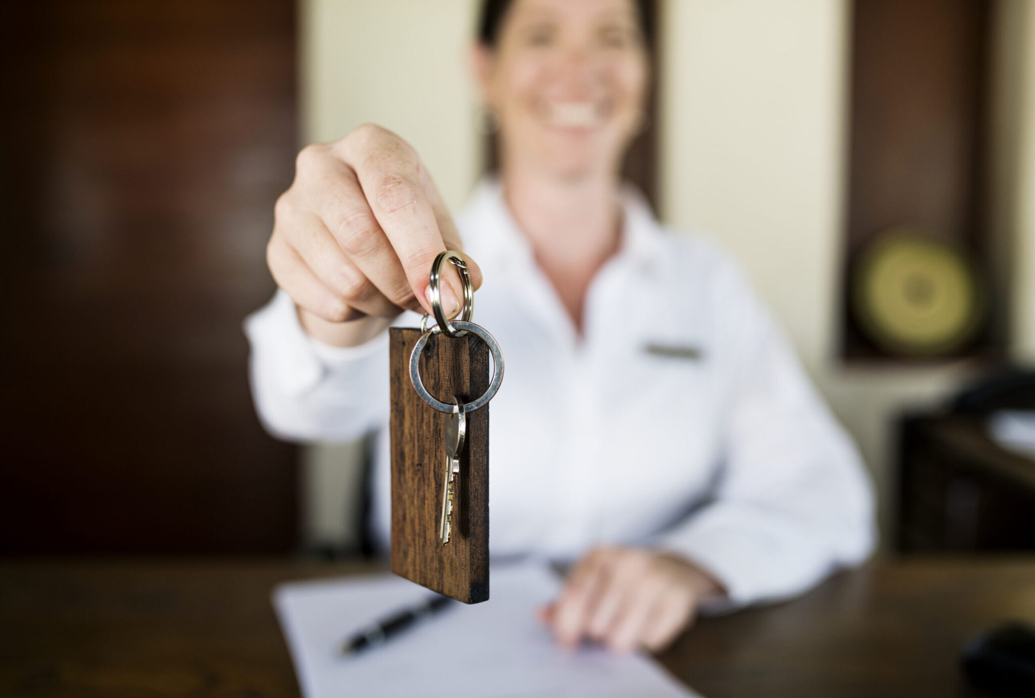 Receptionist holding room key next to hotel phone system