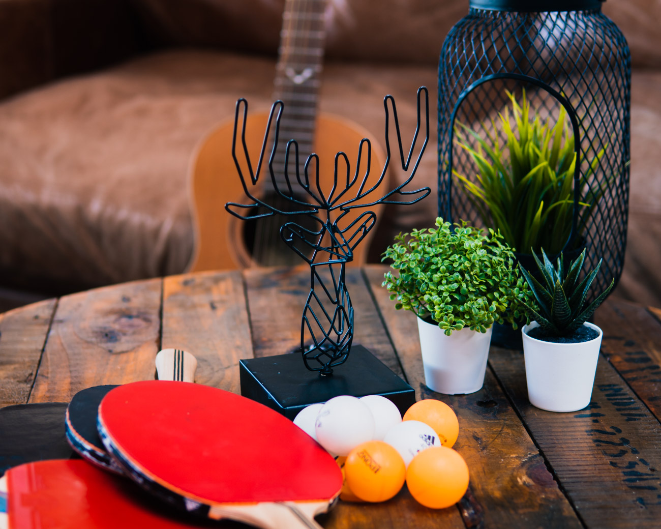 Coffee table with guitar, plants and ping pong bats and balls