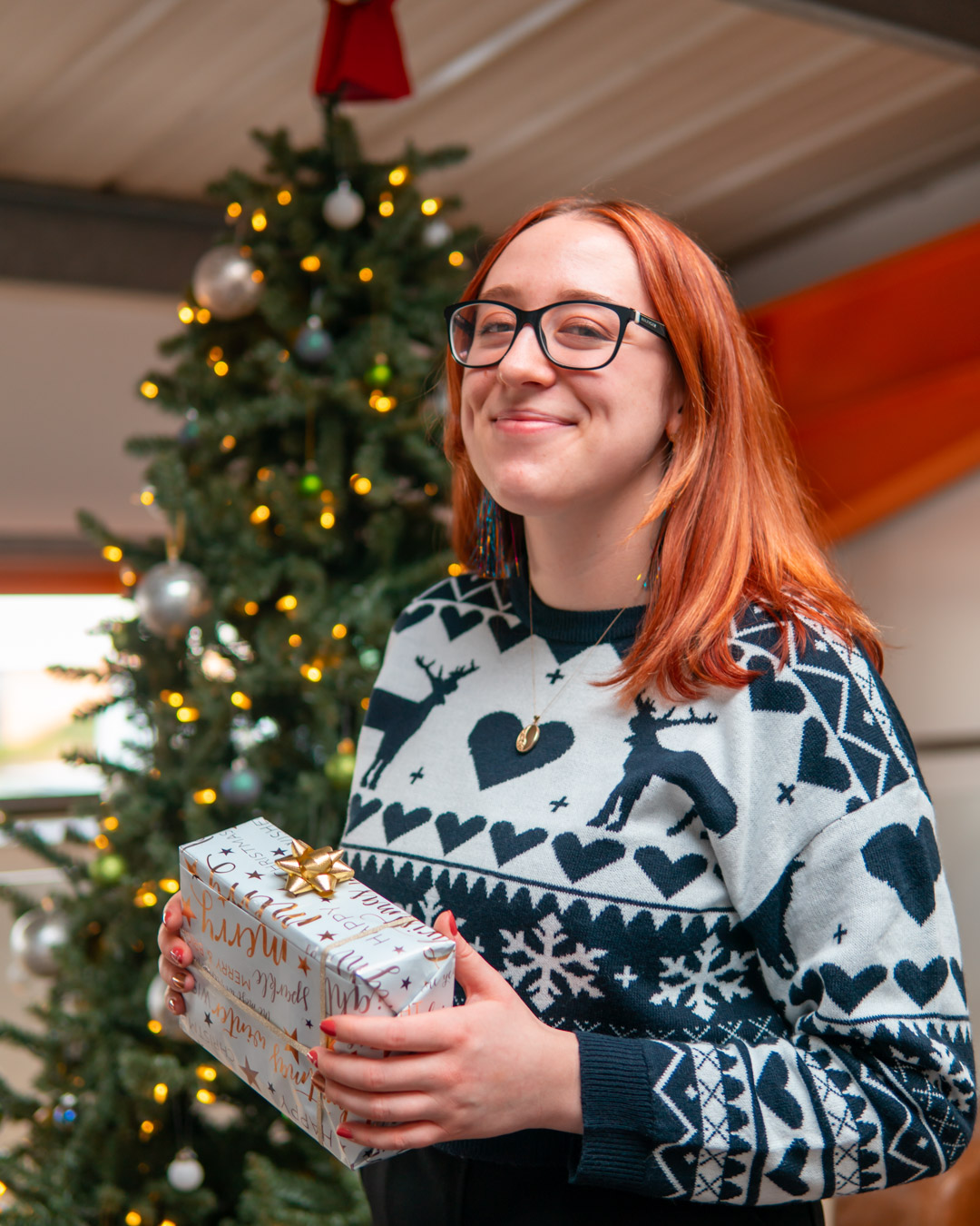 Christmas Jumper Day 2020: Grace wearing Christmas jumper holding a present.